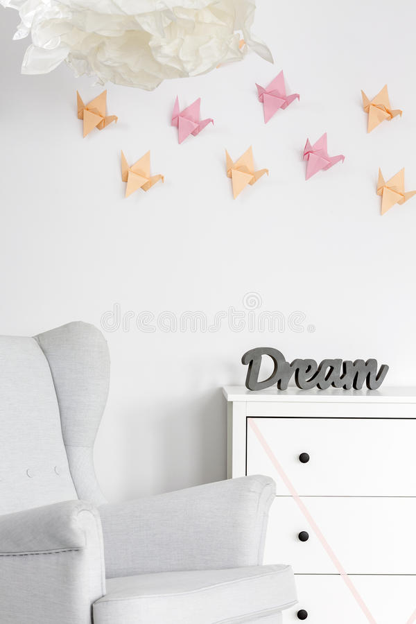Unique 3D origami wall decor. Light home interior with dresser, armchair and origami wall decor stock photography