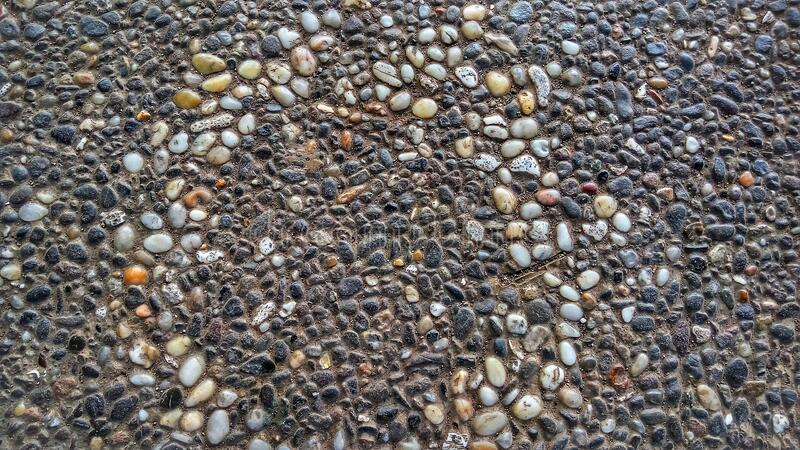 Unique design pattern of floor texture made of small stones. stock image