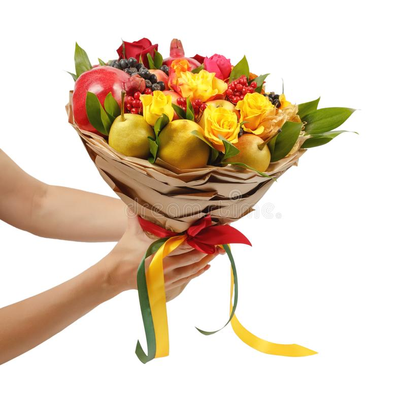 Unique festive bouquet consisting of apples, pears, mountain ash, lemons, viburnum, pomegranates and blooming roses in the hands o. F a girl on a white stock photo
