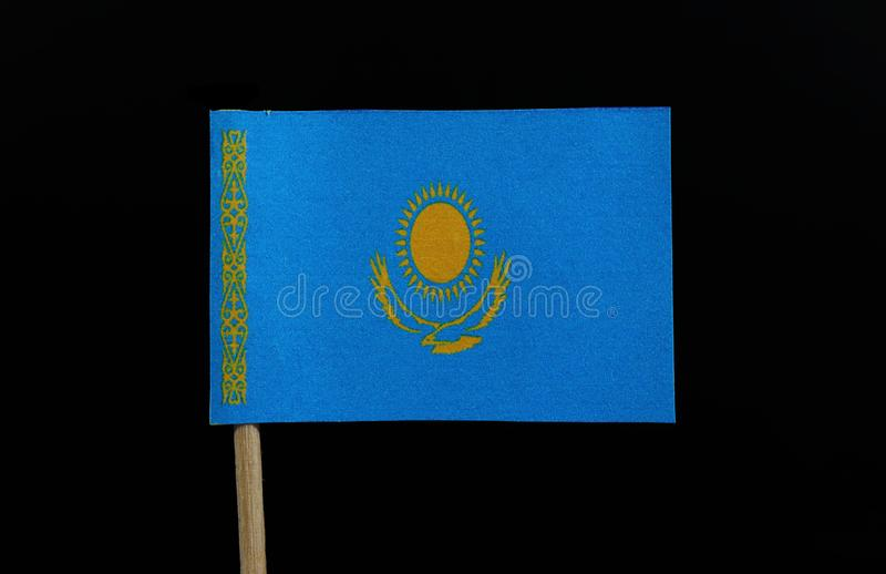 A unique flag of Kazakhstan on toothpick on black background. A gold sun with 32 rays above a soaring golden steppe eagle, both stock image