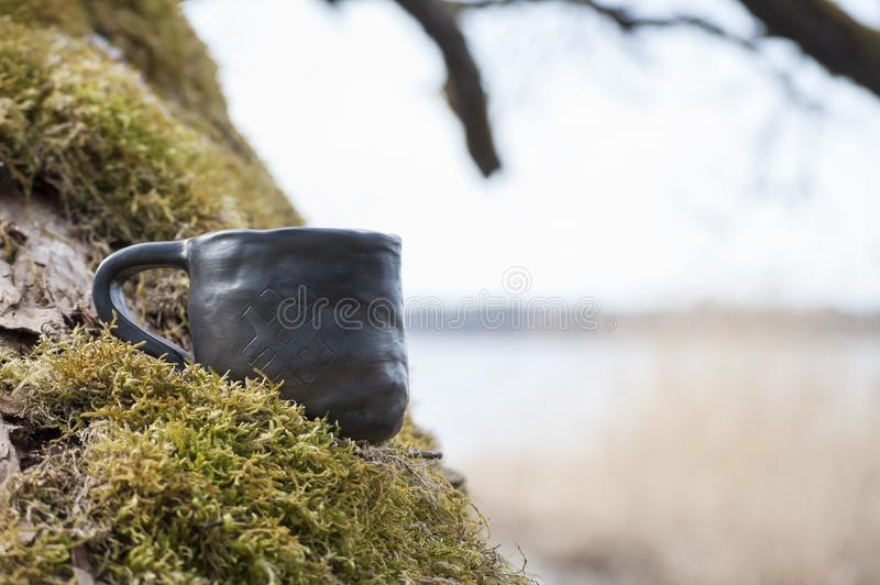 Unique handmade cup with folk sign on moss with blurred lake on background. Beautiful closeup of unique handmade cup with folk sign on green moss with blurred royalty free stock images