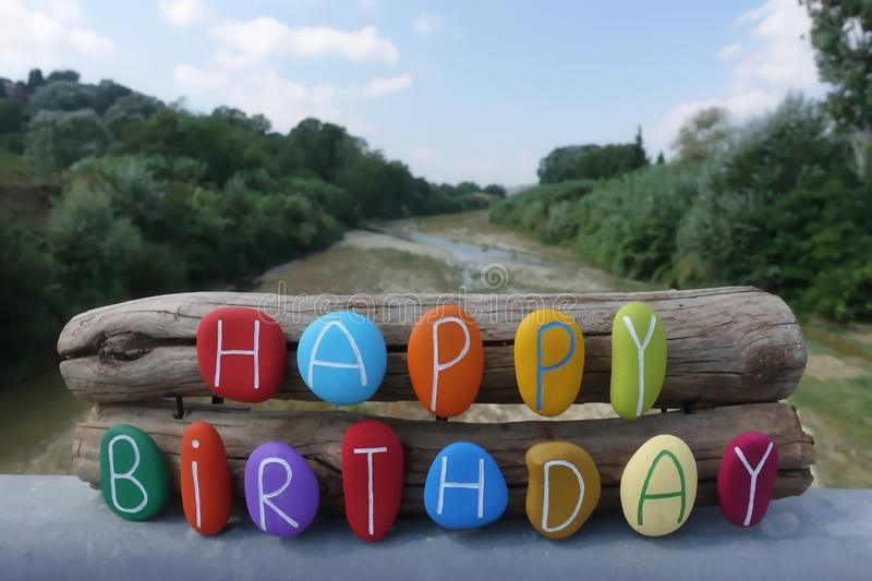 Happy Birthday text with colored stones over two wooden pieces and natural background stock photos