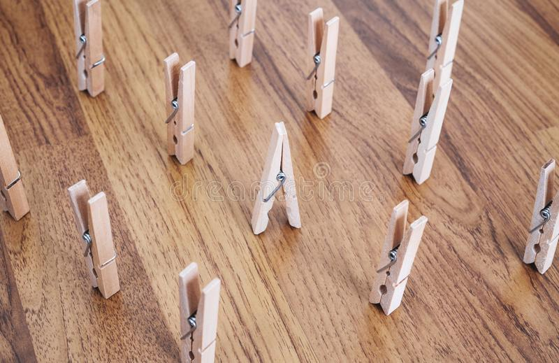 Unique, individuality, leadership and think different concept. One wooden clip difference with other clips on wooden floor stock photography