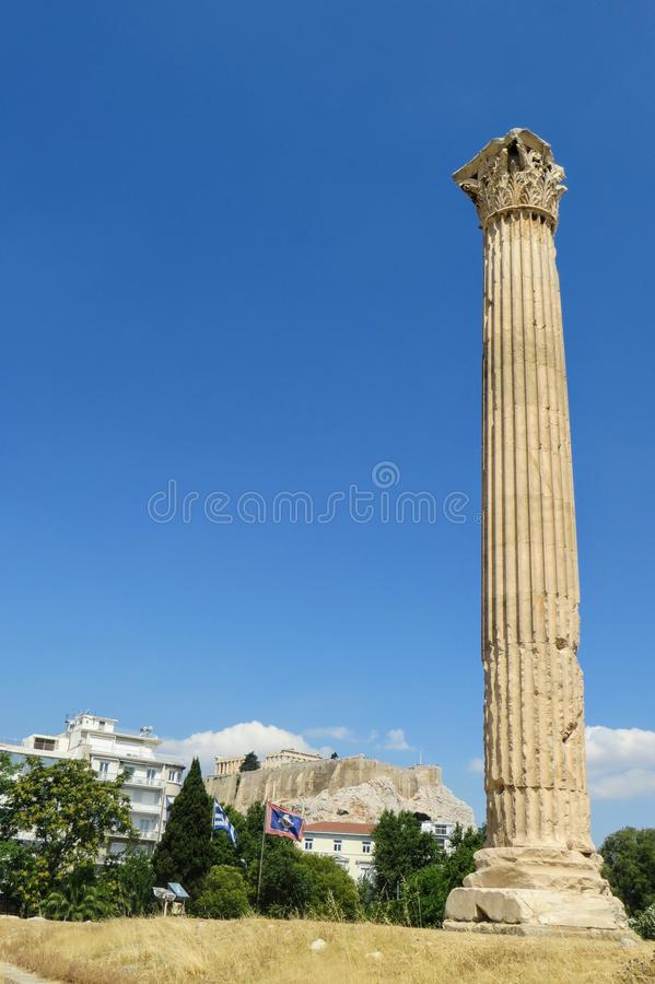 A unique and interesting view of one standing doric column from  the Temple of Olympian Zeus in Athens, Greece. In the distance is the acropolis and parthenon royalty free stock image