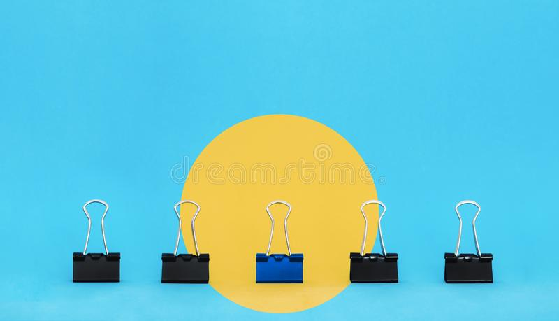 Unique, leadership, individuality, and think different concept. Office supplies, blue binder paper clip stand out of other clips stock photography