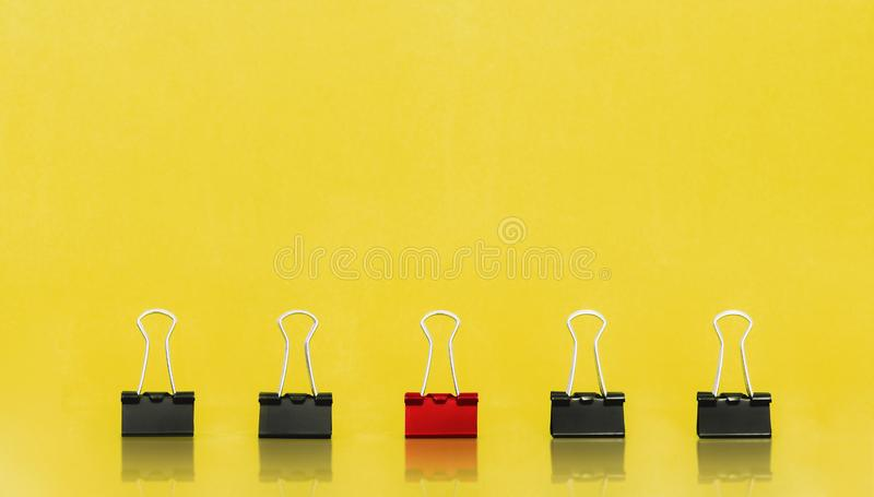 Unique, leadership, individuality, and think different concept. Office supplies, one binder paper clip stand out of other clips royalty free stock image