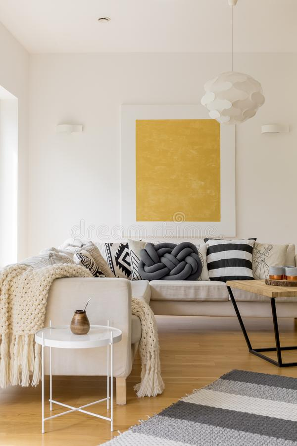 Unique living room. White designed table with calabash and bombilla near beige sofa in unique living room royalty free stock image