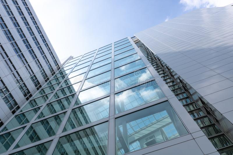 Unique low angle building perspective. Bright sun reflecting on the glass of the modern building. shot in the netherlands royalty free stock photos