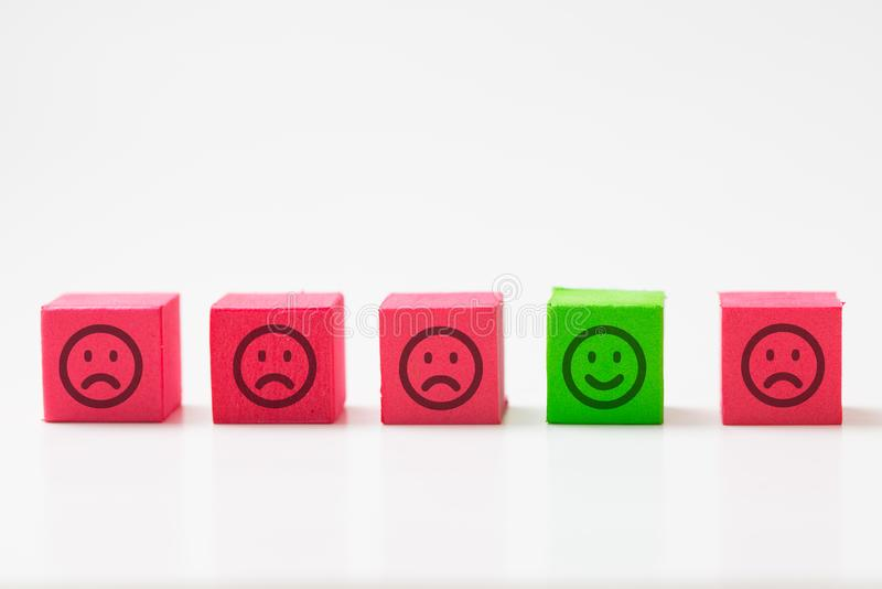 Unique, optimistic, happiness, difference concept using single happy face among many sad faces. Single green smiley happy cube among many sad red other cubes as stock photo