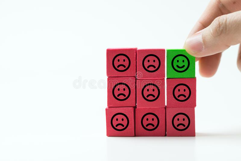 Unique, optimistic, happiness, difference concept using single happy face among many sad faces. Single green smiley happy cube among many sad red other cubes as stock photos