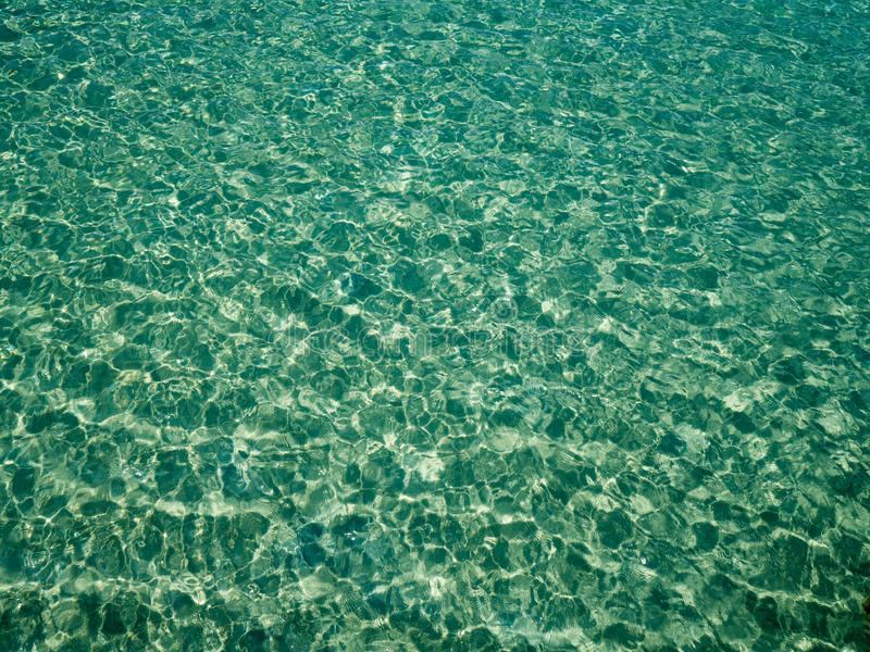 Unique perspective green crystal sea water surface ripple with sun reflection. Water background. Ocean water texture stock images