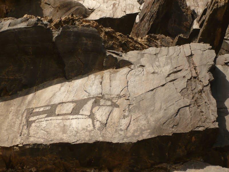 Petroglyphs of bronze depicting an animal royalty free stock photos