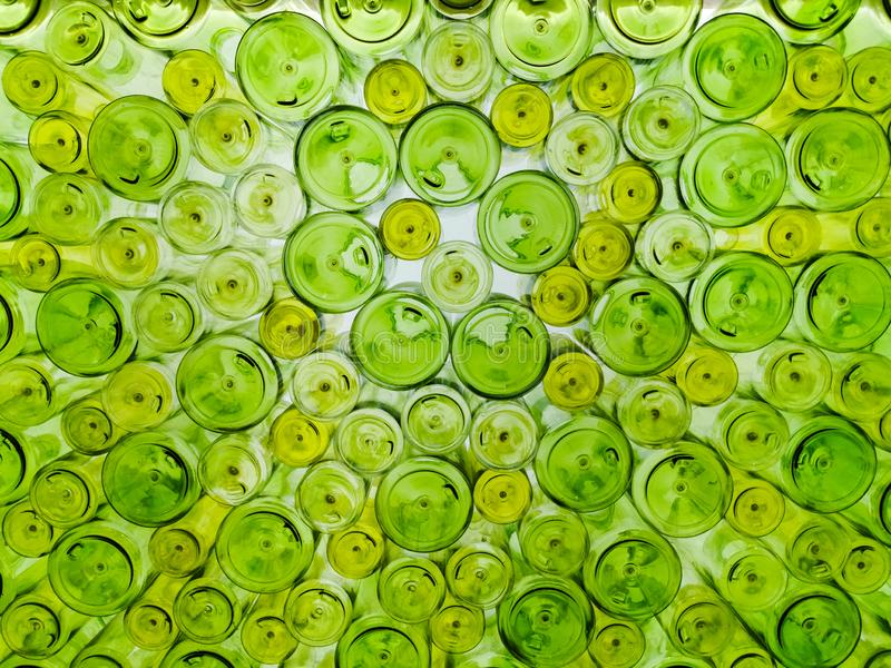 Unique, random and artistic display decorative background with various sizes green glass bottles stock photo