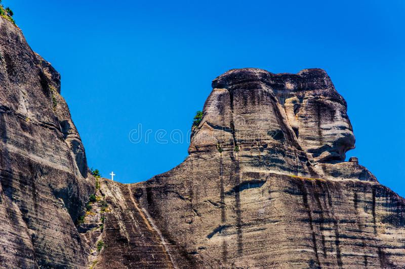 Unique shape formed by hills and white cross of holy trinity at meteora Greece royalty free stock image