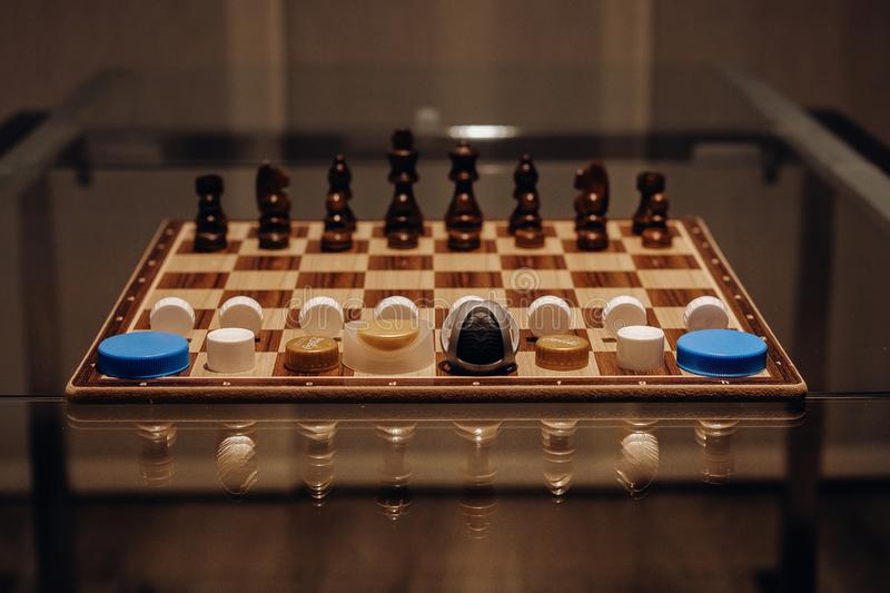 Unique shot of a chess board with brown chess pieces and various bottle caps. A unique shot of a chess board with brown chess pieces and various bottle caps stock image