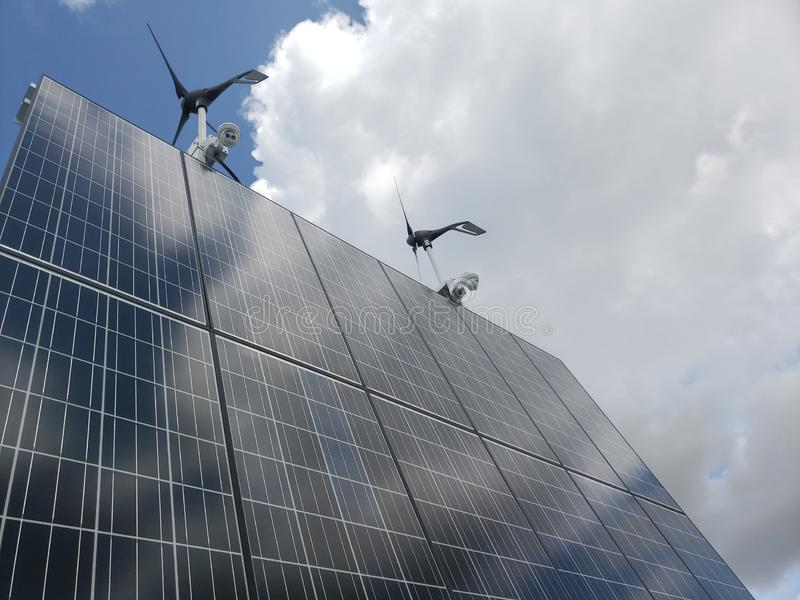 Unique view of an off grid solar wind system. Solar, panels, turbines, cameras, clouds, sky, green, electricity, power, generate, generation, propeller, wind stock images