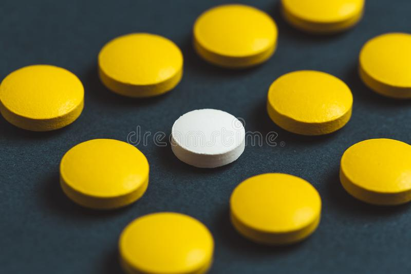 Unique white medicine pill among many yellow ones. Stand out of a crowd, individuality and difference concept. Leadership concept stock photography