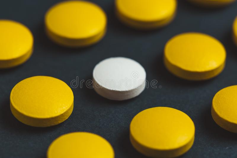 Unique white medicine pill among many yellow ones. Stand out of a crowd, individuality and difference concept. Leadership concept royalty free stock photos