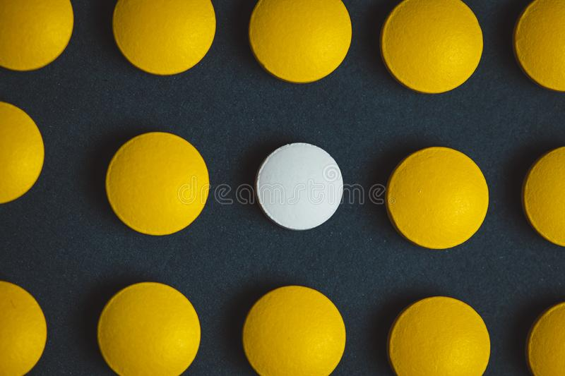 Unique white medicine pill among many yellow ones. Stand out of a crowd, individuality and difference concept. Leadership concept stock photo