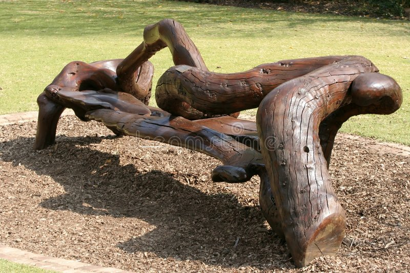 Unique Wooden Bench. Unique park bench made out of twisted tree trunks royalty free stock images