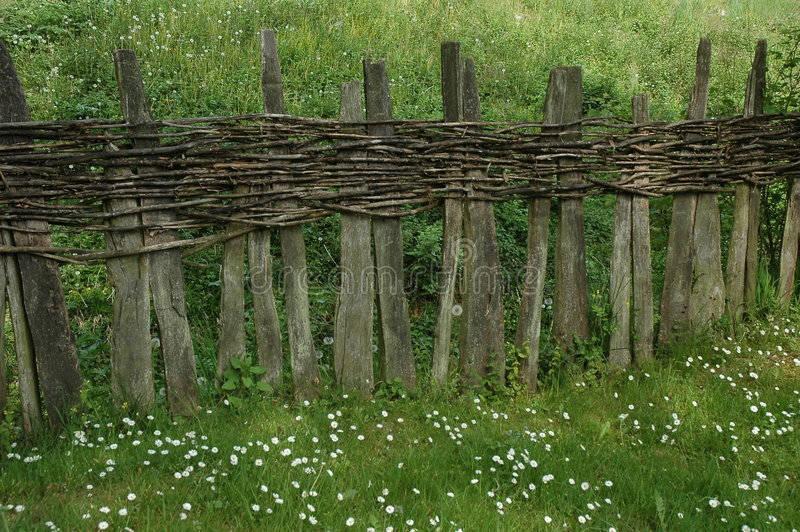 Unique wooden fence. Details of a rough wooden fence created from wooden slabs and interwoven branches stock photo