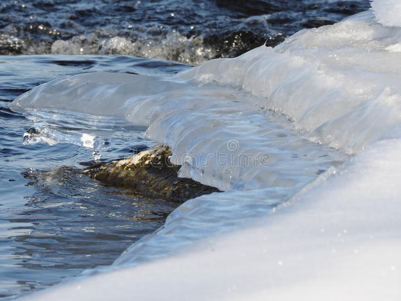 Unique formation of a growing snow covered ice shelf with the Ottawa River running swiftly under it. Uniquely shaped formation of a growing snow covered ice royalty free stock image