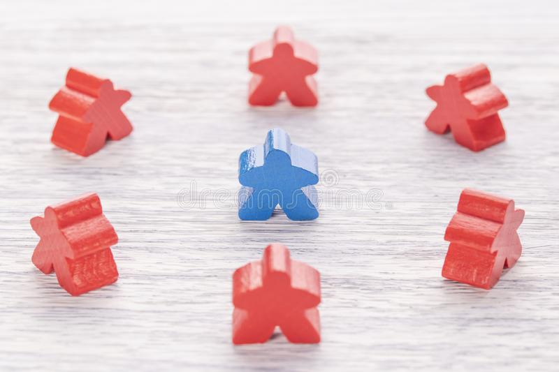Uniqueness, individuality and difference. Blue wooden figure in a crowd of different color stock photo