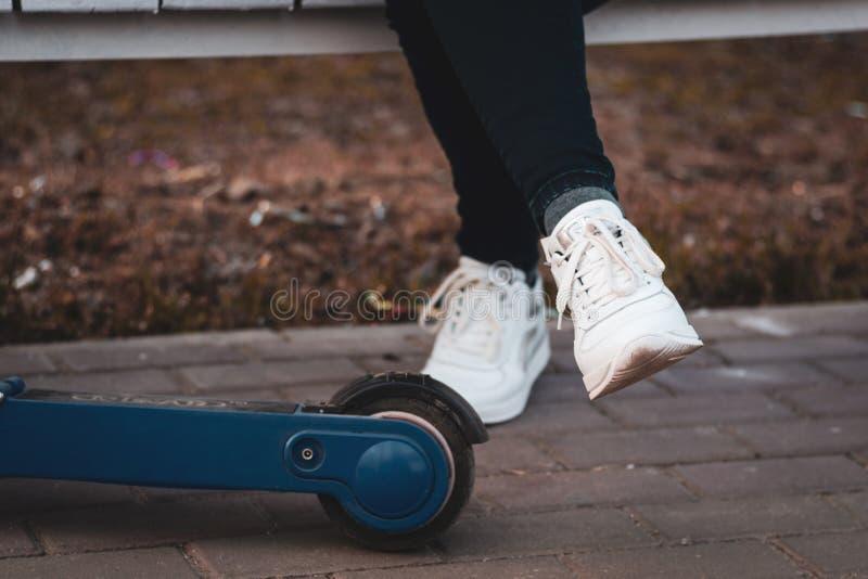 Unisex- ben i vita gymnastikskor bredvid hjulet av en elektrisk sparkcykel royaltyfri foto
