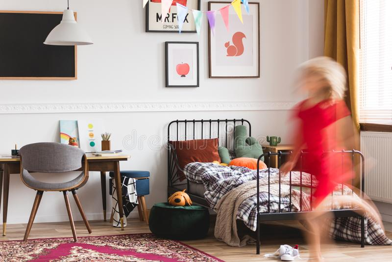 Unisex- rum med retro möblemang, konstverk och enkel säng för metall arkivfoton