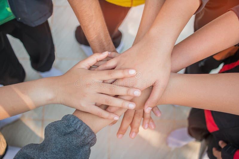 Unità e concetto di lavoro di squadra: Gruppo di mani degli amici insieme Punto di vista superiore dei giovani asiatici che un la immagini stock libere da diritti