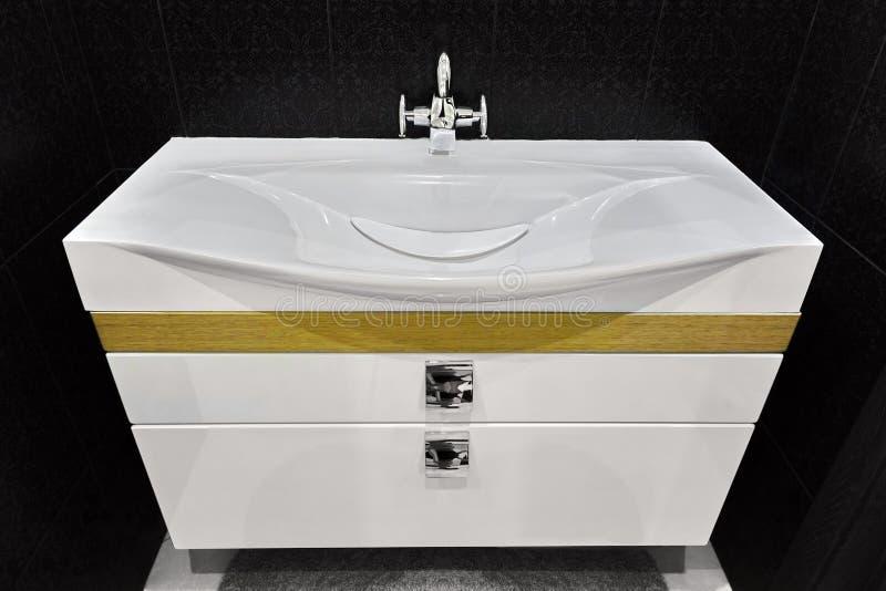Unité blanche moderne de bassin de vanité dans la salle de toilette carrelée noire photo libre de droits