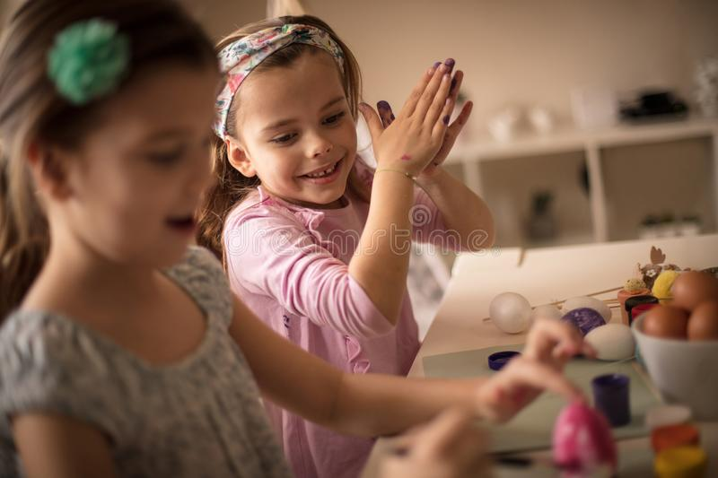 Unite forces for Easter preparations. Little girls coloring Easter egg royalty free stock photo