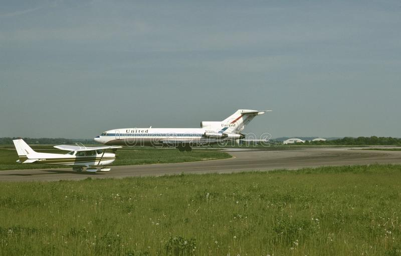 United Airlines Boeing B-727 en een Cessna 172 op een mooie middag bij de Internationale Luchthaven van Pittsburgh, Pennsylvania  royalty-vrije stock foto