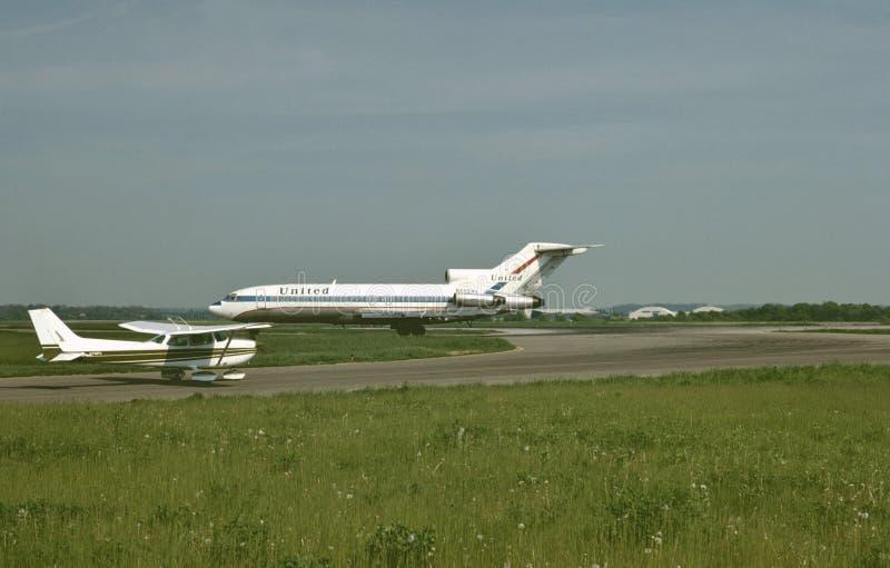 United Airlines Boeing B-727 y un Cessna 172 en una tarde hermosa en el aeropuerto internacional de Pittsburgh, Pennsylvania en m foto de archivo libre de regalías