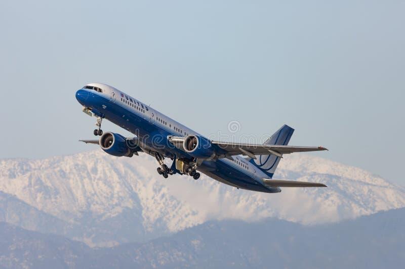 United Airlines Boeing 757 het vertrekken Los Angeles Internationale Luchthaven met sneeuw afgedekte bergen op de achtergrond stock foto's