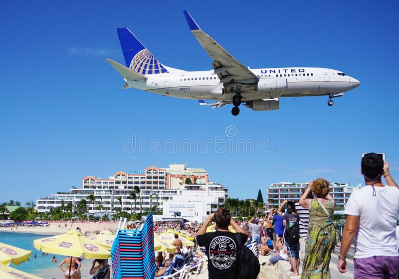 A United Airlines Boeing 737 lands over Maho Beach in St Martin stock image