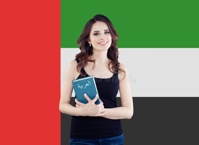 United Arab Emirates concept with happy woman student with book against the UAE flag background. Travel and learn arabic language.  royalty free stock images