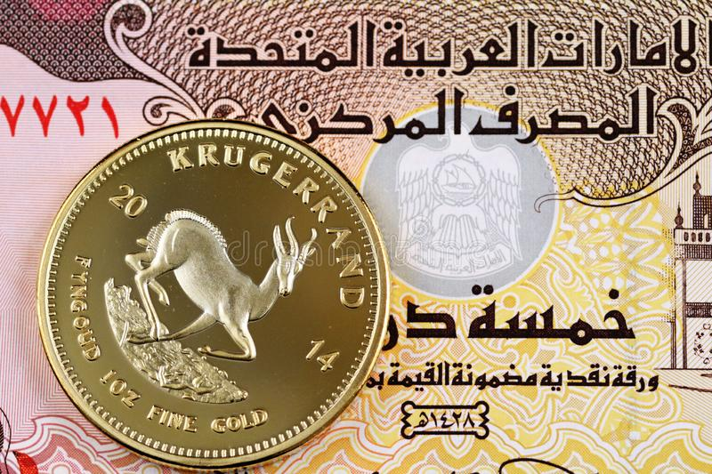 Five UAE dirham bank note with a golden Krugerrand coin. A United Arab Emirates five dirham note with a golden Krugerrand coin stock photography