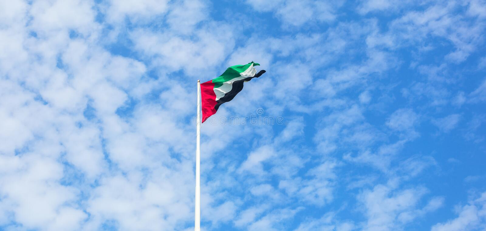 United Arab Emirates flag flying against beautiful blue sky with clouds. UAE celebrates it`s national day on 2nd December every. Year stock photography