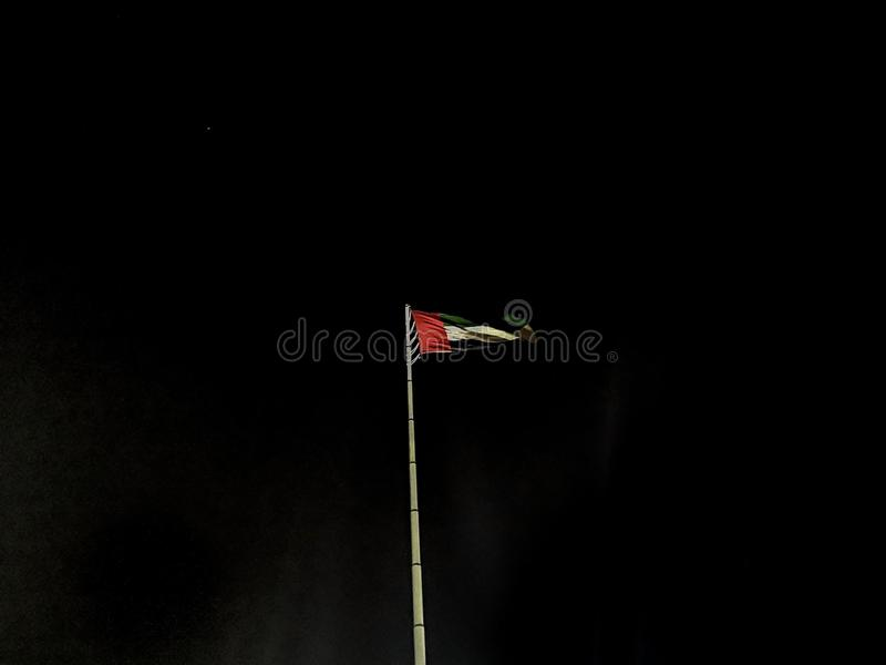 The United arab emirates flag waving at night.  royalty free stock photography