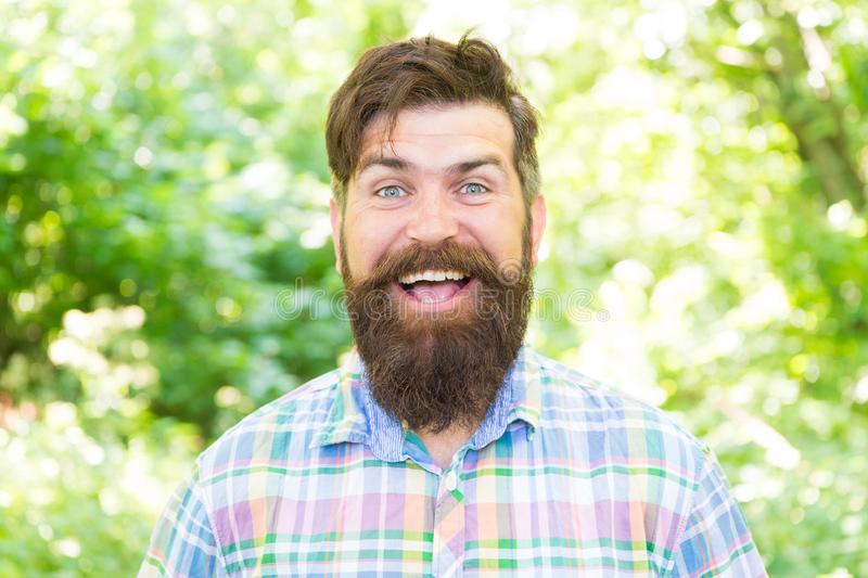United with environment. Handsome lumberjack. Man beard and mustache in summer forest. Summer vacation concept. Man. Bearded hipster green trees background. Guy stock photography