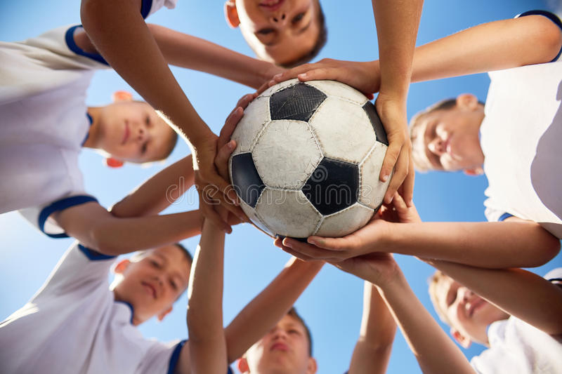 United Football Team. Low angle view of boys in junior football team standing in circle holding ball together against blue sky, focus on ball stock photos