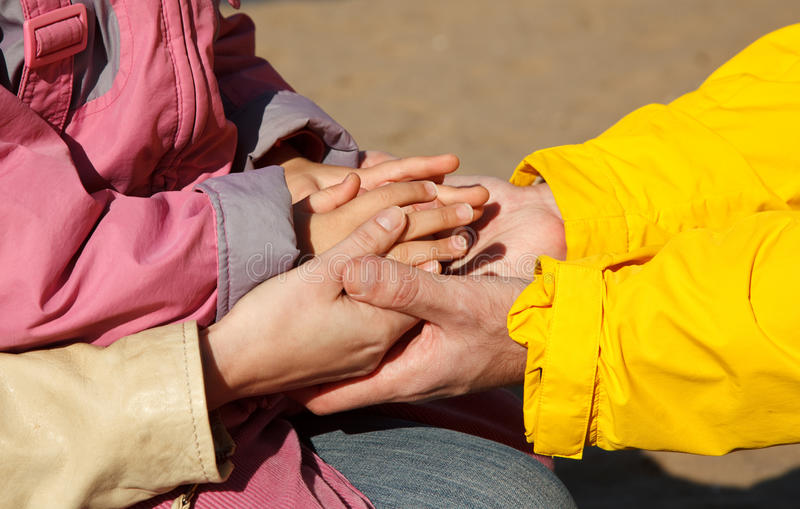 United hands as symbol of family unity. United hands of adults and child as symbol of family unity. Photo outdoors stock photos