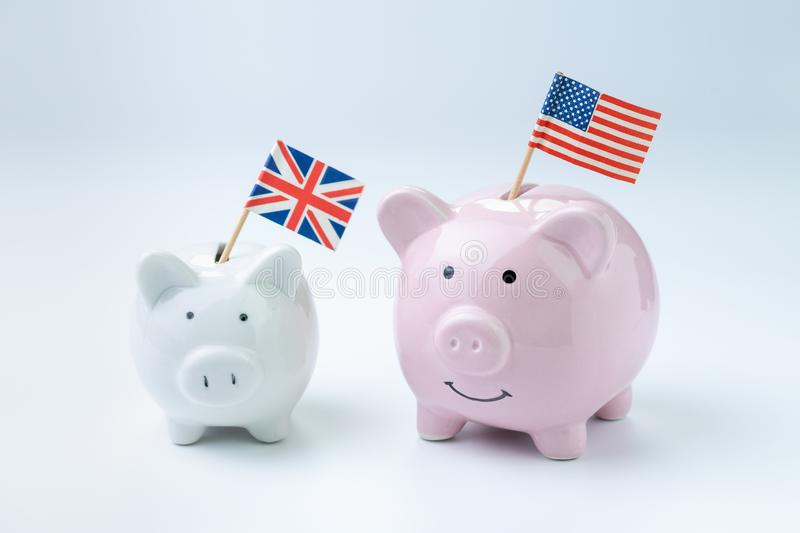 United Kingdom Brexit and US America budget, economics and investment concept, happy smile pink piggy bank with the UK national. Flag isolated on white and blue royalty free stock photos