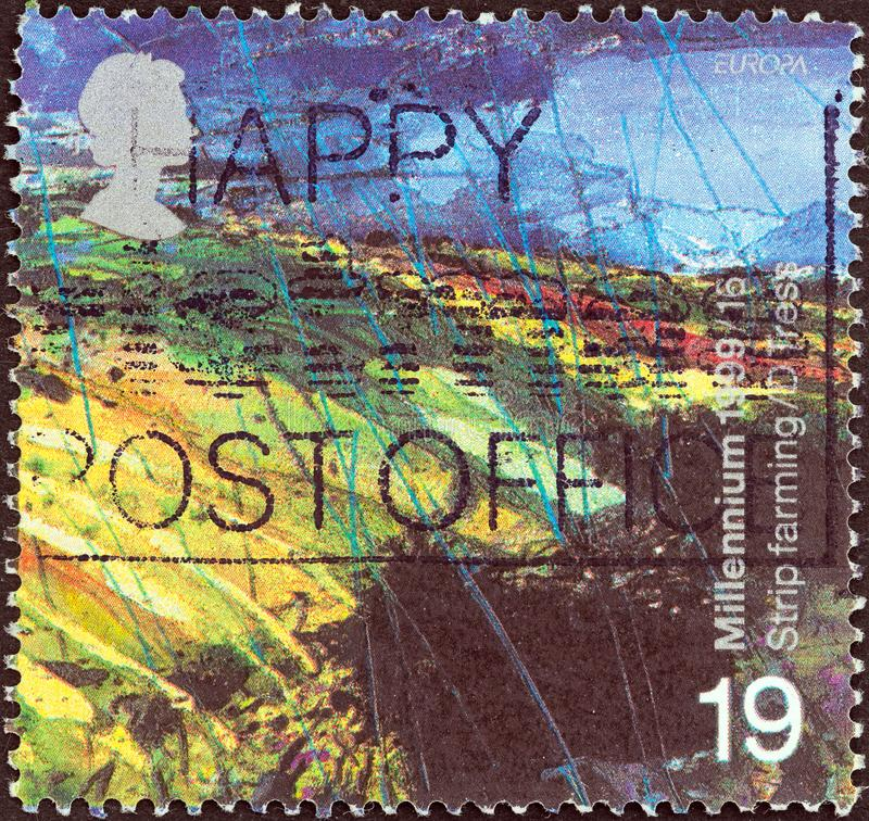 UNITED KINGDOM - CIRCA 1999: A stamp printed in United Kingdom shows The Farmers` Tale, Upland Landscape, circa 1999. royalty free stock photography