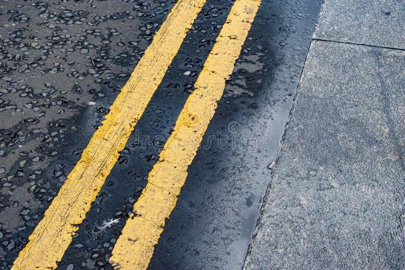 United Kingdom Double Yellow Line. Road Marking next to kerb on asphalt / tarmac road stock photo