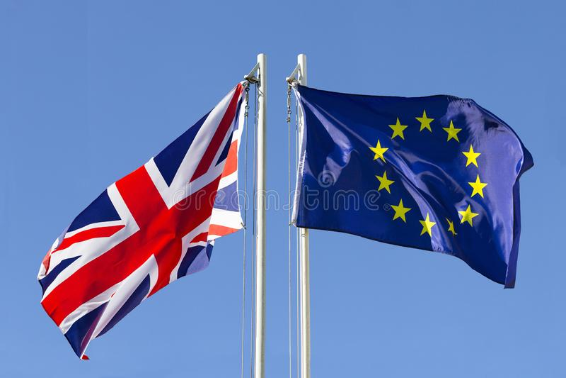 United Kingdom flag vs. European Union flag on flagpole royalty free stock images