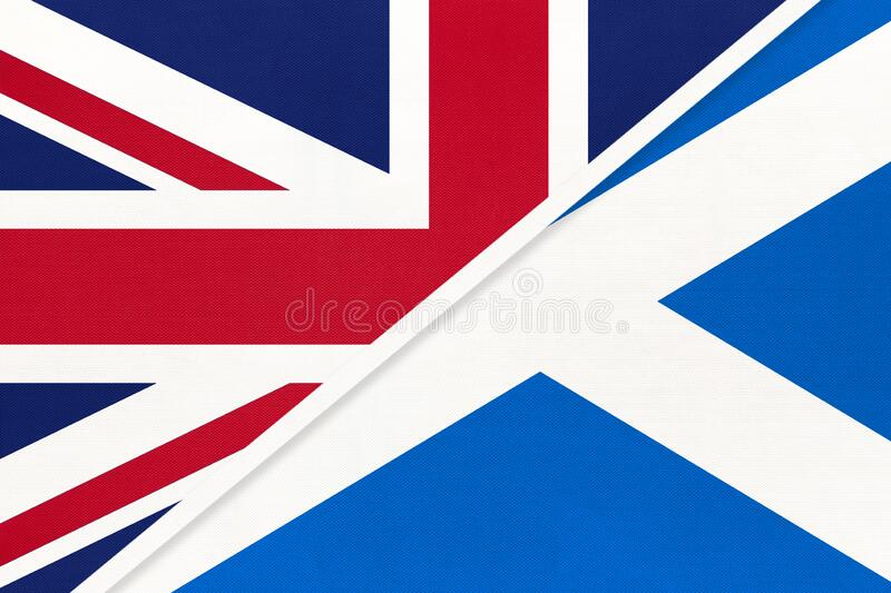 United Kingdom of Great Britain vs Scotland national flag from textile. Relationship between two european countries. United Kingdom of Great Britain and Ireland royalty free stock photography