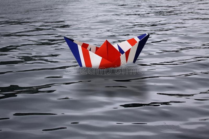United Kingdom sailing alone in the sea like a paper ship made as the English flag Union Jack - Brexit concept showing England lea royalty free illustration