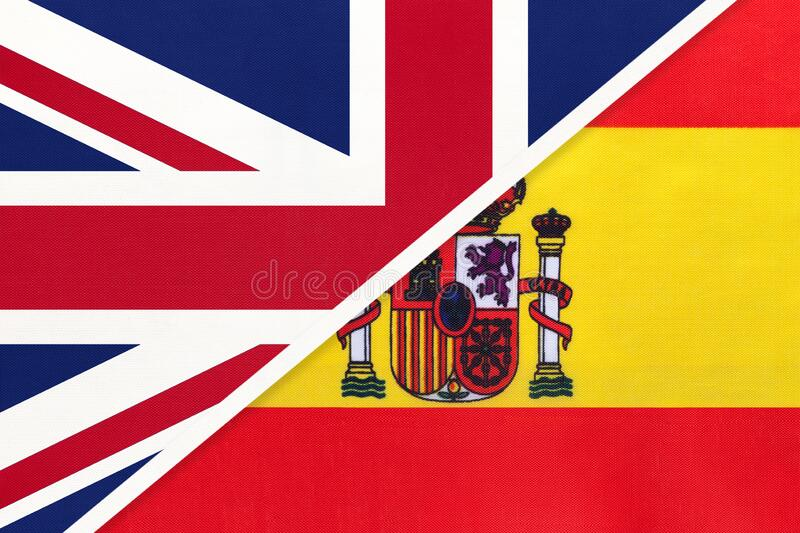 United Kingdom vs Spain national flag from textile. Relationship between two european countries. United Kingdom of Great Britain and Ireland vs Spain national royalty free stock photography